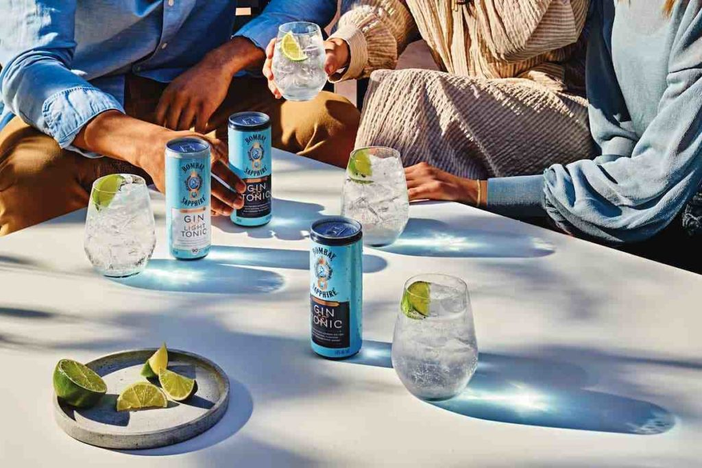 People around a table holding cans of Bombay Sapphire Canned Gin & Tonic
