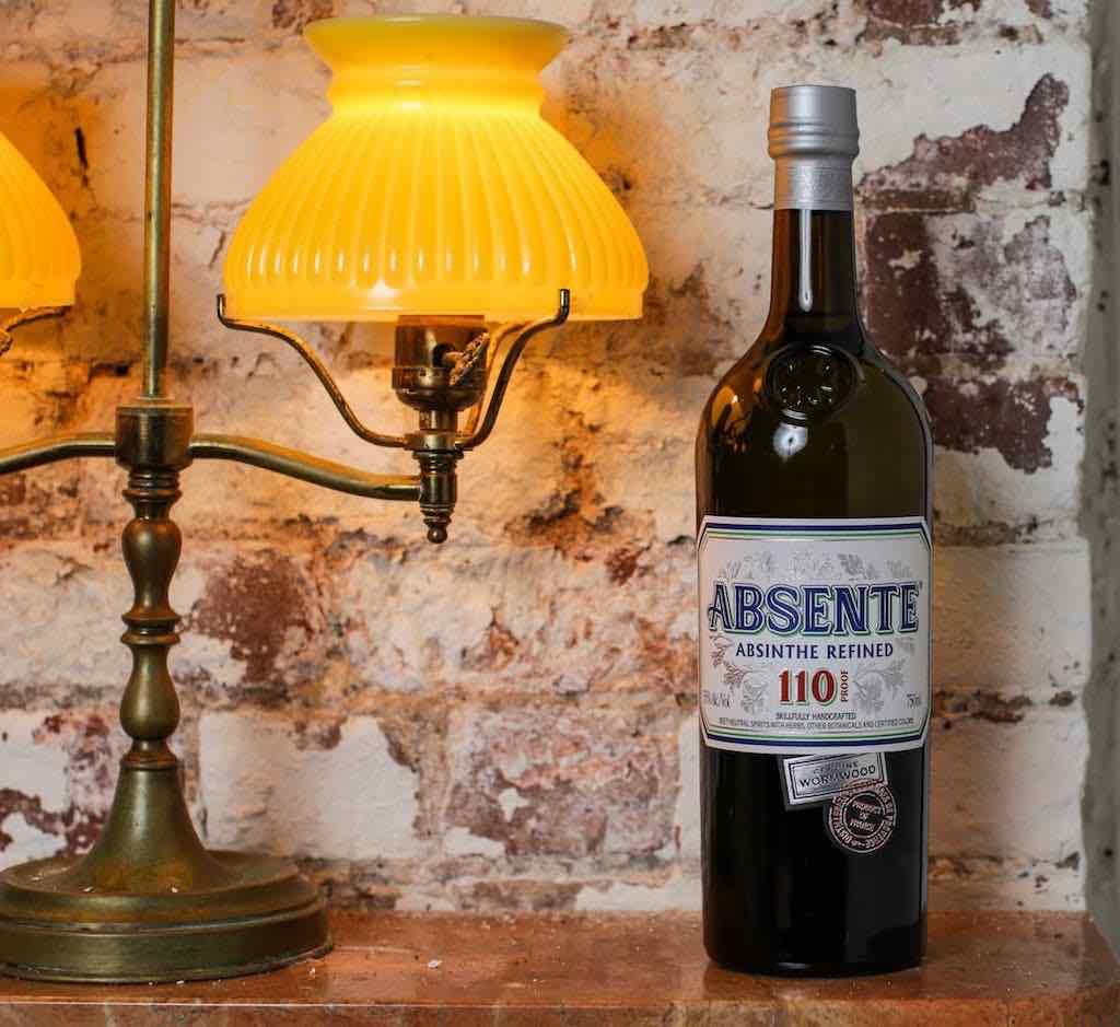 absetne refined absinthe bottle next to lamp