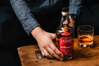 hand holding a bottle of o.h. ingram river aged rye whiskey