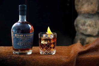 Milam & Green Texas Manhattan Cocktail with bourbon bottle