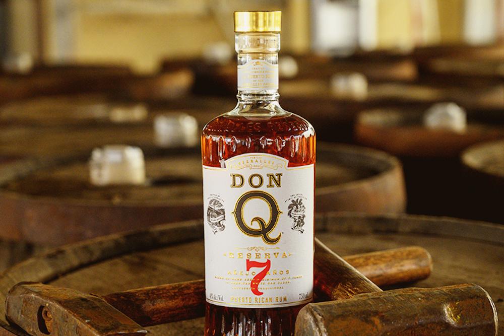 Don Q Reserva 7 rum bottle on an oak barrel