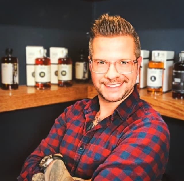 Nicholas Pollachi in a checkered shirt, standing in front of whisky bottles