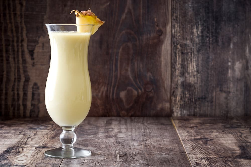 dirty banana cocktail garnished with a pineapple wedge